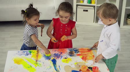 Three little artists enjoying their messy painting in hand