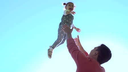otec : Slow motion of handsome father throwing his adorable daughter in the air Dostupné videozáznamy