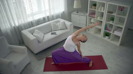 harcos : Bald yogis shifting from warrior pose to revolved triangle pose Stock mozgókép