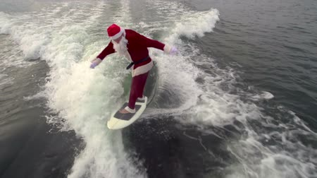 santa : Above view of man is Santa Claus disguise wakesurfing professionally gesticulating thumbs up