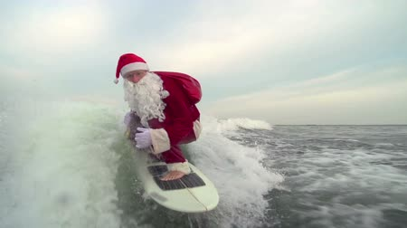 santa : Man in Santa Claus costume with gift bag freestyling on wake surf touching water