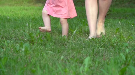 Low angle of woman walking with child barefoot on grass 影像素材