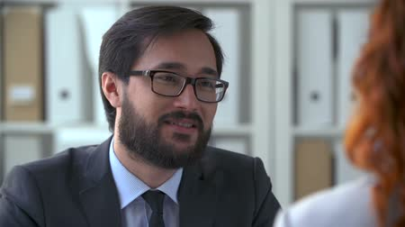 discussão : Close up of male face talking to unidentified woman sitting with her back to the camera at business negotiations Stock Footage