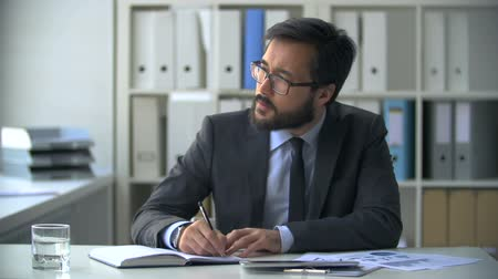 impostos : Asian businessman at the office desk copying information to his notebook