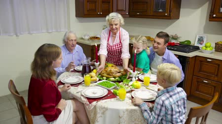 vacsora : Family of three generations gathered for festive meal, grandmother putting roasted turkey on the table and everybody applauding