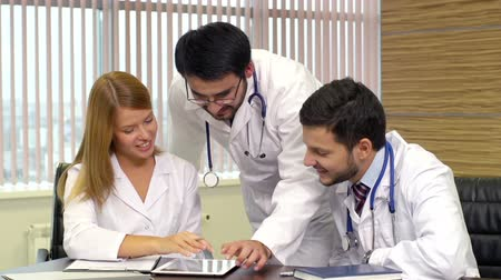 physicians : Close up of medical workers in the staffroom browsing the internet on digital tablet
