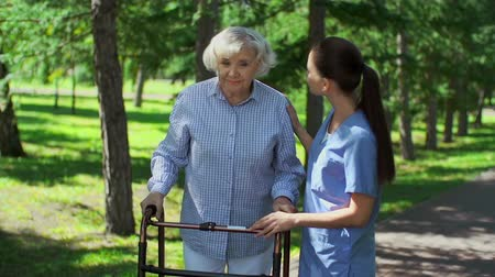 caregiver : Close up of caring nurse explaining to senior patient how to use walker