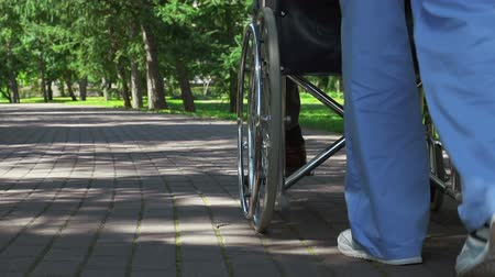 kurtarma : Low section shot of caregiver driving wheelchair of patient along the lane