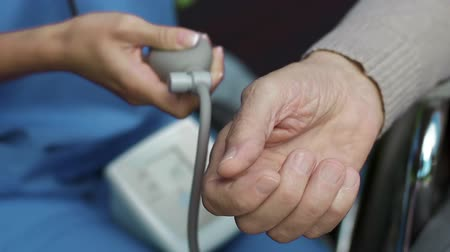 tıbbi bakım : Extreme close up of patient's hand during doctor's pumping pulsometer to measure blood pressure