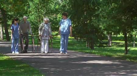 segítség : Two young caregivers accompanying two senior patients strolling outdoors with walkers