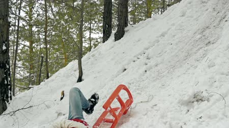 imprudence : Teenage boy riding sledge down the steep hill falling whirlabout