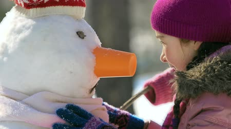 протирать : Close up of little girl rubbing her nose against nose of snowman