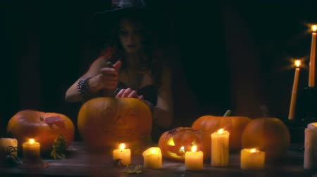 dynia : Close up of gorgeous witch cutting out pulp from pumpkin to make jack o lantern