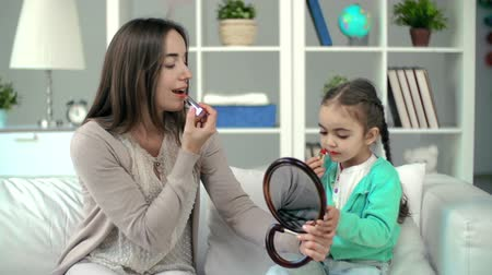 dikmek : Mother showing daughter lipstick applying technique, girl failing to rouge correctly but having lots of fun