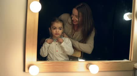 dikmek : Mother fitting necklace to her daughter in front of the lighted make up mirror in the dark room