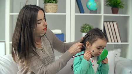 braid hairs : Close up of girl with her lips rouged applying face powder on her face while her mother cuing her hair in a pigtail