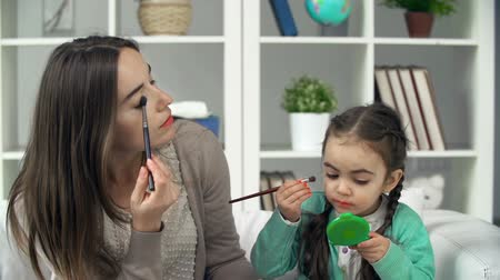 dikmek : Close up of mother teaching her little daughter to apply eye shadows correctly Stok Video