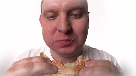 saturado : Fish eye close up of fat male face devouring hamburger against white background