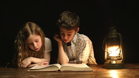 rodzeństwo : Close up of two kids sitting in the darkness at the desk and reading a huge book together Wideo