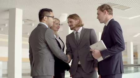 síťování : Slow motion of four business people greeting each other with business-like handshakes