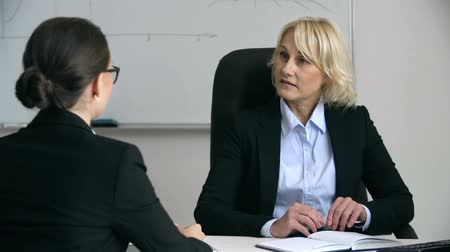 Bossy woman talking to subordinate employee seated with her back to the camera