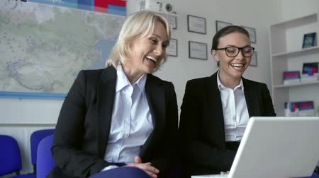смеющийся : Two business women laughing at something on the screen of laptop