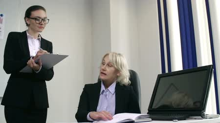 буфер обмена : Bossy lady seated at the desk dictating tasks to young secretary standing nearby