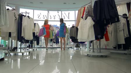 butik : Two shoppers walking with bags full of purchases out of the boutique Stok Video
