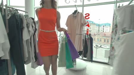 lojas : Girl with shopping bags walking along the clothes shop with French windows in slow motion