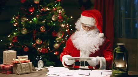 rakás : Santa Claus finishing his reply letter and browsing digital tab