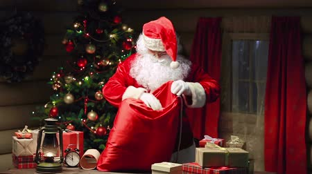 santa : Santa Claus packing gift boxes in sack and waving hand