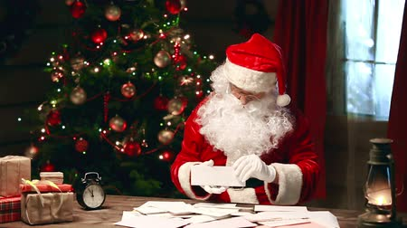 Санта шляпе : Santa Claus sitting at the table and reading wish letters from kids
