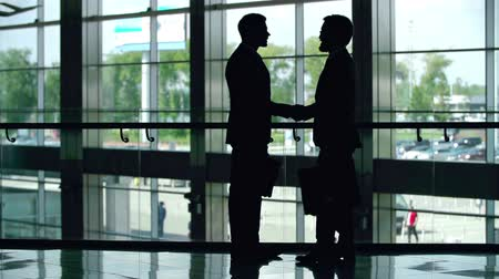 встреча : Silhouettes of two businessmen greeting each other with a handshake