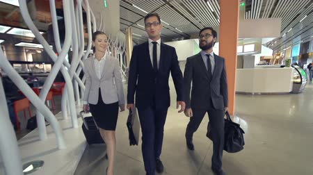 lobi : Slow motion of three business people approaching camera, two colleagues joining them in the airport terminal