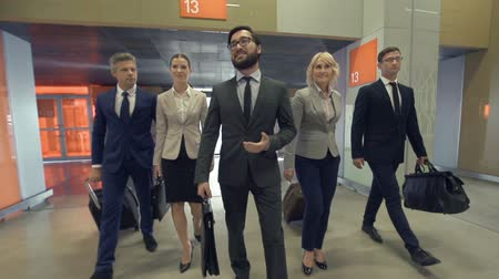viagens de negócios : Business team of five approaching camera after arrival at the airport, team leader walking in front of other colleagues