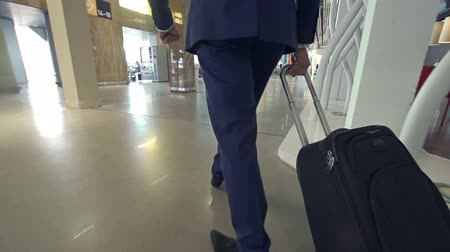 bagagem : Slow motion of man with luggage walking along airport terminal with his back to the camera