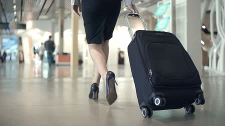 lounge : Low section of business woman walking with her back to the camera along airport waiting room in slow motion