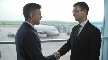 colaboração : Two business men introducing themselves with a handshake standing at the airport panoramic window