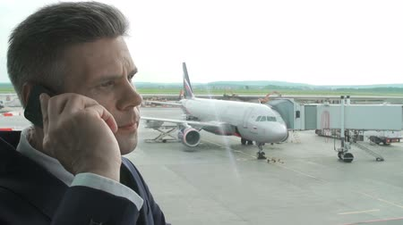 telescopic : Close up of businessman making a phone call at the airport window