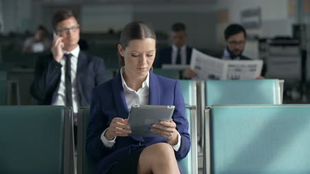 viagens de negócios : Focus on business woman with digital tablet waiting for a flight, other passengers in the background Stock Footage