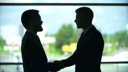 negocjacje : Outlines of two businessmen shaking hands near the window