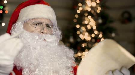 santa : Close up of Santa Claus dissatisfied with news in letter Stock Footage