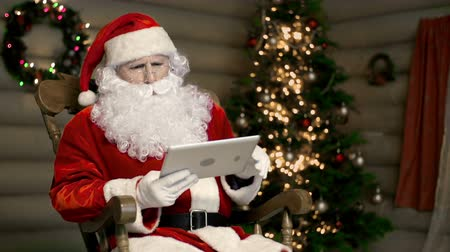 Санта шляпе : Santa Claus using digital tablet and seeing something disgraceful on the screen Стоковые видеозаписи