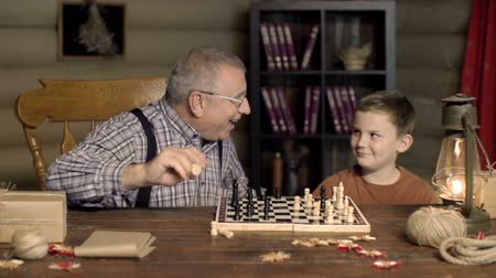 захват : Grandpa happy to capture chess pawn of his grandchild, shocked by his counterstrike