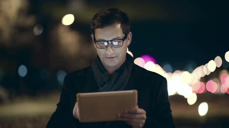 latest : Man standing outdoors at night and using digital tablet
