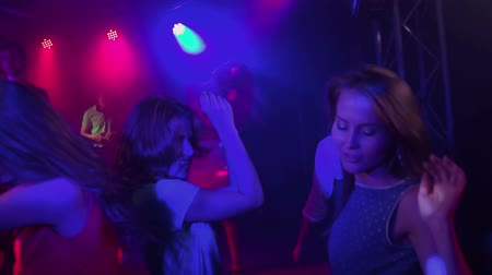 tłum : Handheld shot of crowd going all out dancing at night club in slow motion Wideo