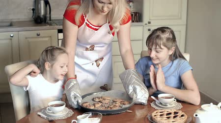 kötény : Mother of two girls putting the tray with homemade cookies on the dinner table Stock mozgókép