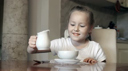 porselen : Little girl pouring light cream in her cup of tea
