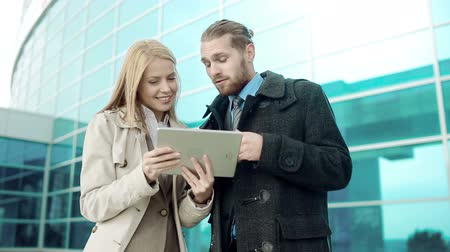 collaboration : Low angle of business partners browsing internet on touchscreen device standing in the street Stock Footage