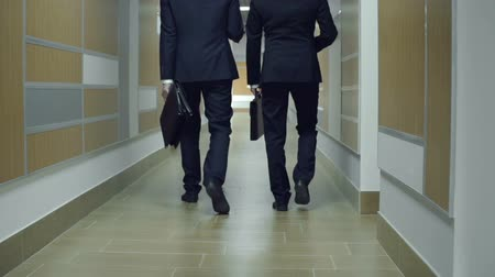 walk behind : Camera following two anonymous businessmen having discussion in office corridor